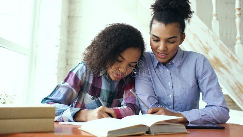 Moça de cabelo encaracolado adolescente da raça misturada que senta-se na concentração da tabela focalizada aprendendo lições e s foto de stock royalty free