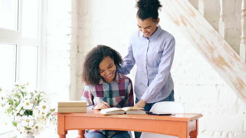 Moça de cabelo encaracolado adolescente da raça misturada que senta-se na concentração da tabela focalizada aprendendo lições e s fotografia de stock royalty free
