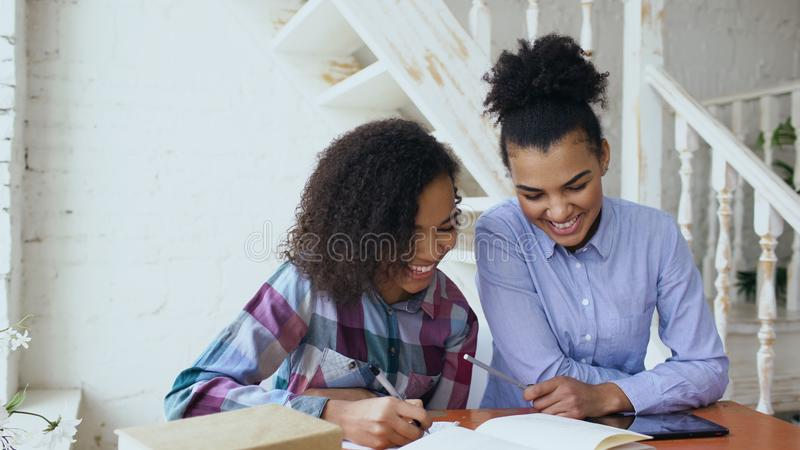Moça de cabelo encaracolado adolescente da raça misturada que senta-se na concentração da tabela focalizada aprendendo lições e s imagens de stock royalty free