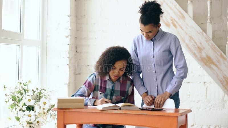 Moça de cabelo encaracolado adolescente da raça misturada que senta-se na concentração da tabela focalizada aprendendo lições e s imagens de stock