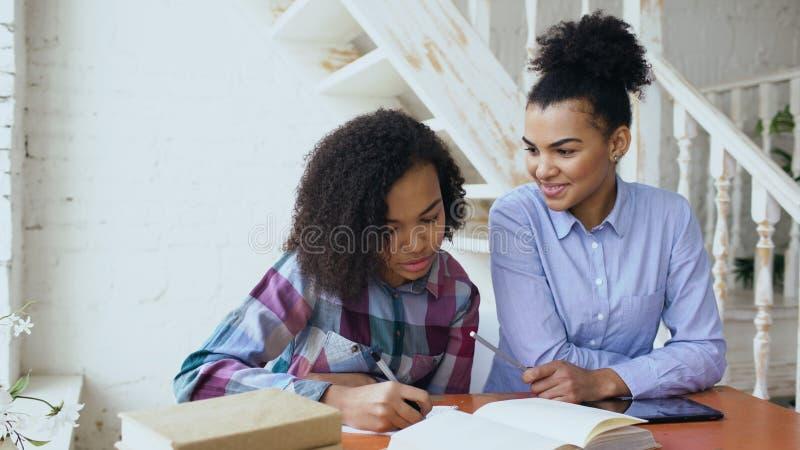 Moça de cabelo encaracolado adolescente da raça misturada que senta-se na concentração da tabela focalizada aprendendo lições e s foto de stock