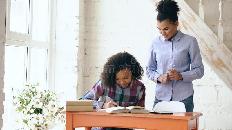 Moça de cabelo encaracolado adolescente da raça misturada que senta-se na concentração da tabela focalizada aprendendo lições e s fotografia de stock
