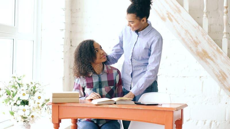 Moça de cabelo encaracolado adolescente da raça misturada que senta-se na concentração da tabela focalizada aprendendo lições e s imagem de stock