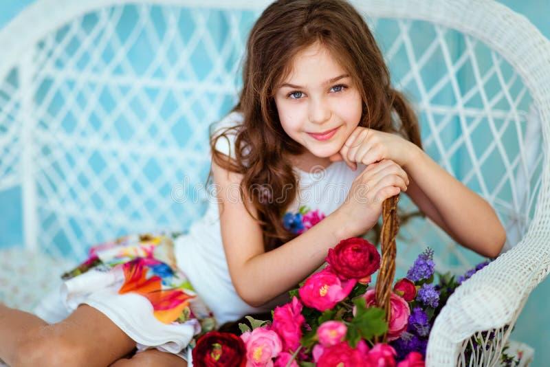 Moça de cabelo encaracolado de sorriso muito doce que senta-se perto tomar sol imagem de stock