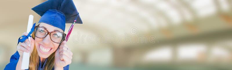 Moça de graduação pateta na bandeira do tampão e do vestido imagem de stock