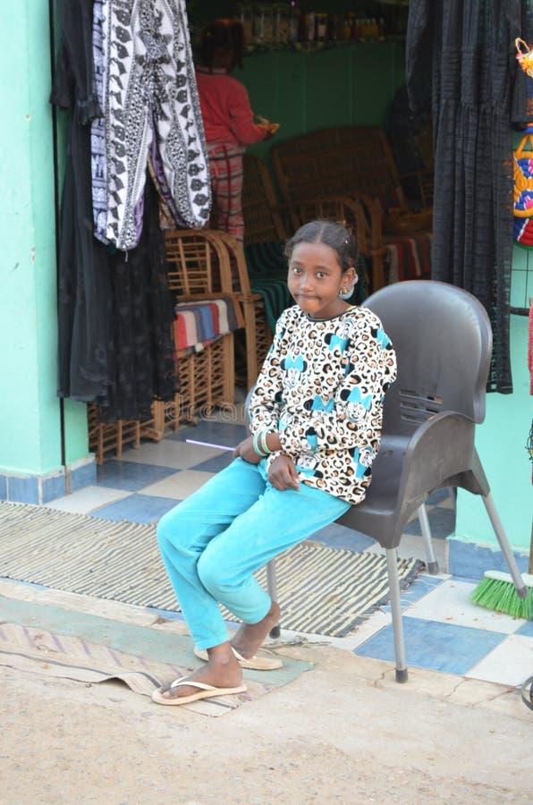 Moça de sorriso assentada fora da loja em Egito imagens de stock royalty free