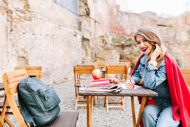 A moça de sorriso louro está sentando-se na tabela do jardim, amigos de espera e está fazendo-se anotações no caderno imagens de stock