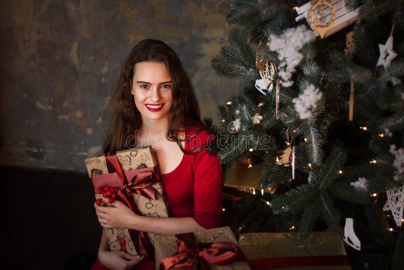 Moça de sorriso no vestido vermelho com presentes e caixas de presente sob a árvore de Natal foto de stock royalty free