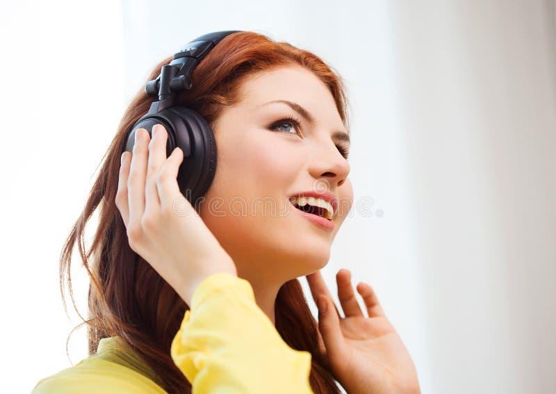 Moça de sorriso nos fones de ouvido em casa imagens de stock royalty free