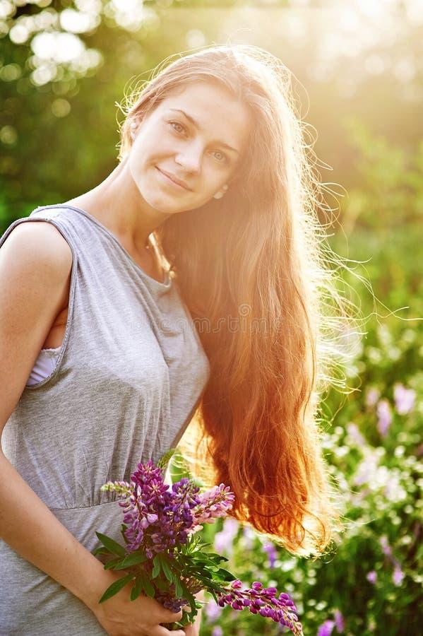 Moça de sorriso que guarda um grupo de flores do lupine no campo ensolarado do verão foto de stock