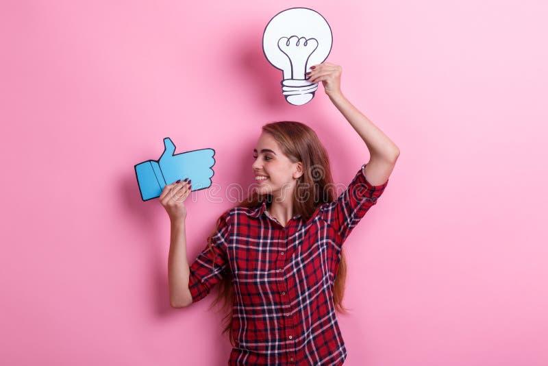 Moça de sorriso que guarda uma imagem de um bulbo e um sinal e uma vista do polegar-acima dele Conceito da ideia fotos de stock