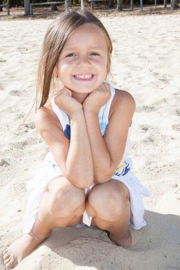 A moça de sorriso senta-se no verão da praia da areia fotografia de stock royalty free