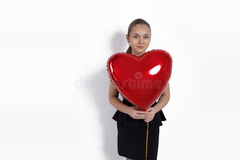 Moça de Valentine Beauty, adolescente com o retrato vermelho do balão de ar, isolado no fundo fotos de stock royalty free