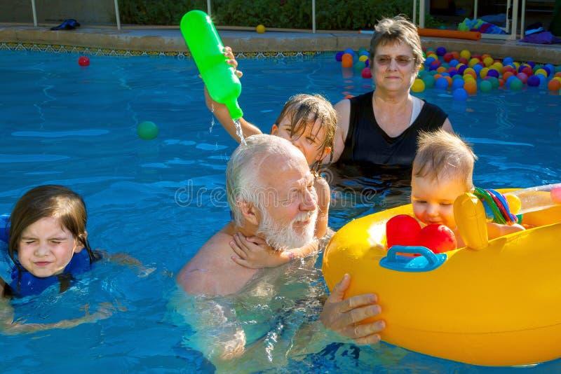 A moça derrama a água sobre a cabeça de seu avô como grande fotografia de stock royalty free
