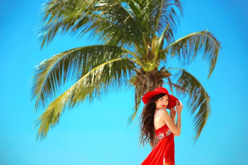 Moça despreocupada da beleza com o chapéu vermelho que relaxa no bea tropical imagem de stock royalty free