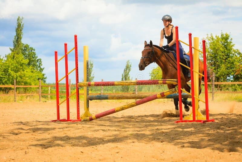 Moça do jóquei que faz o cavalo que salta através do obstáculo foto de stock royalty free