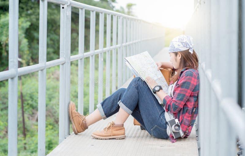 A moça do moderno que guarda o mapa disponível e senta-se na estrada de ferro da ponte imagens de stock