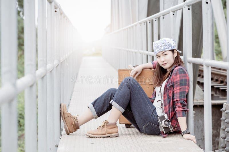 A moça do moderno senta-se na estrada de ferro da ponte com bagagem do vintage imagem de stock royalty free