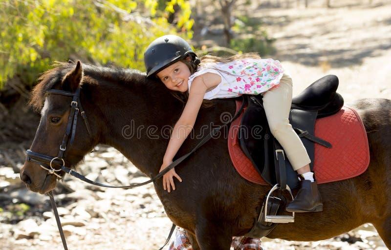 Moça doce que abraça o capacete vestindo feliz de sorriso do jóquei da segurança do cavalo do pônei nas férias de verão imagens de stock royalty free