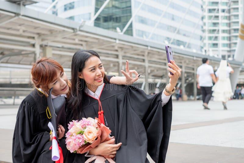 A moça dois toma a uma foto com o telefone na celebração um graduati imagem de stock royalty free