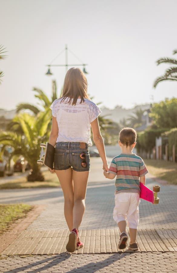Moça e criança bonito com skates exteriores foto de stock royalty free