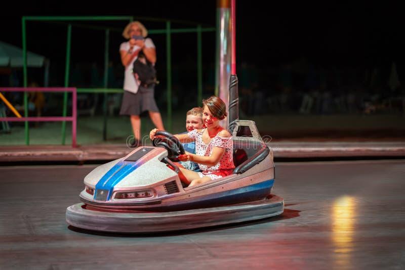 Moça e menino que conduzem um carro abundante em um parque de diversões na noite foto de stock