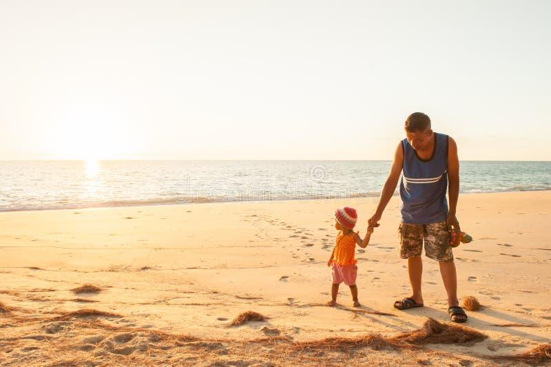 Moça e pai que veem o oceano pela primeira vez no sol fotografia de stock