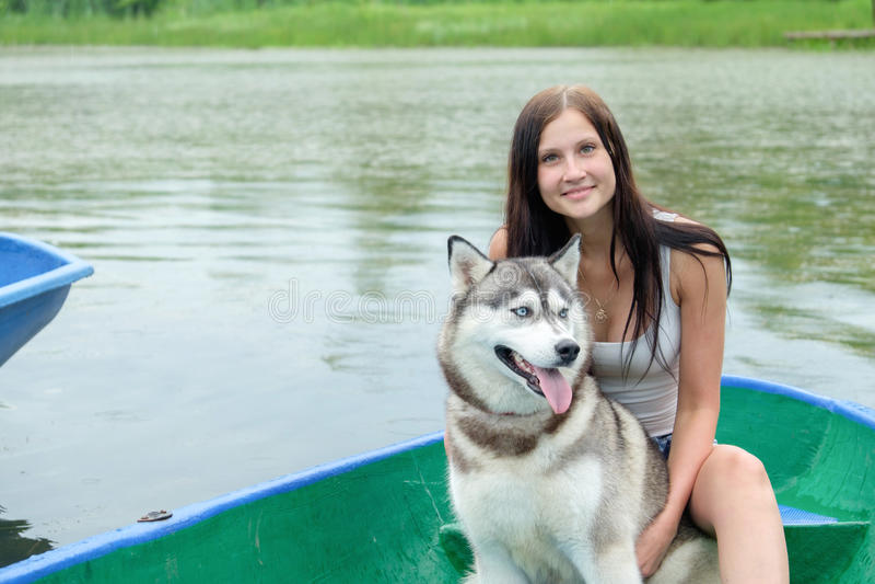 A moça e seu cão de puxar trenós do cão estão sentando-se em um parque perto do lago no verão fotografia de stock royalty free