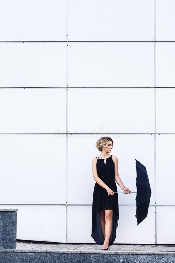 Moça elegante em um vestido preto e com um guarda-chuva que levanta contra uma parede cinzenta fotografia de stock royalty free