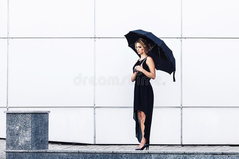 Moça elegante em um vestido preto e com um guarda-chuva que levanta contra uma parede cinzenta imagens de stock royalty free