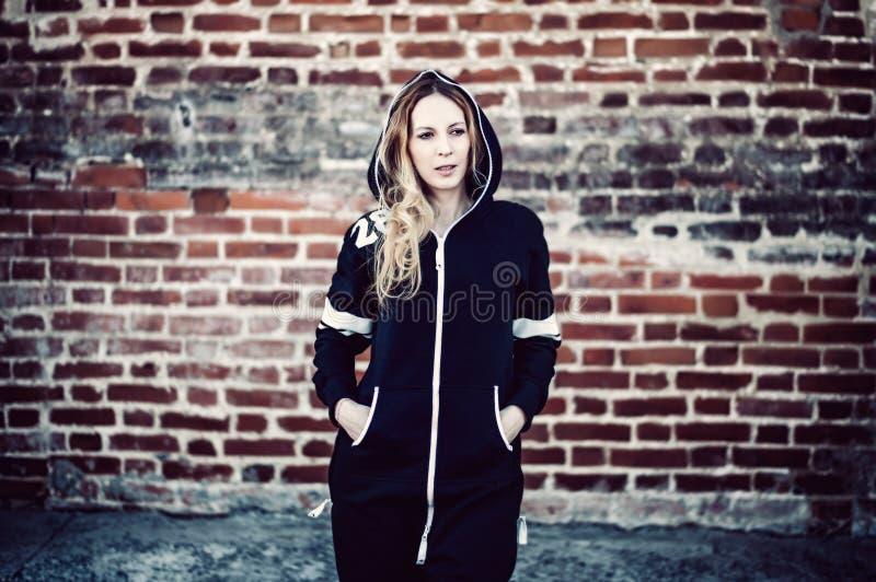 Moça em macacões pretos no fundo da parede de tijolo na cidade imagens de stock royalty free