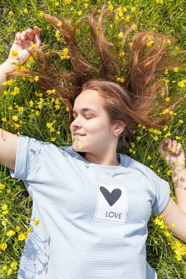 Moça em um campo do gramado com flores amarelas foto de stock royalty free