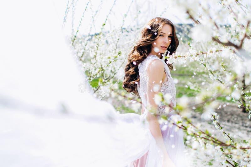 Moça em um jardim florescido branco dos pêssegos em um vestido e em uma composição brancos fotografia de stock