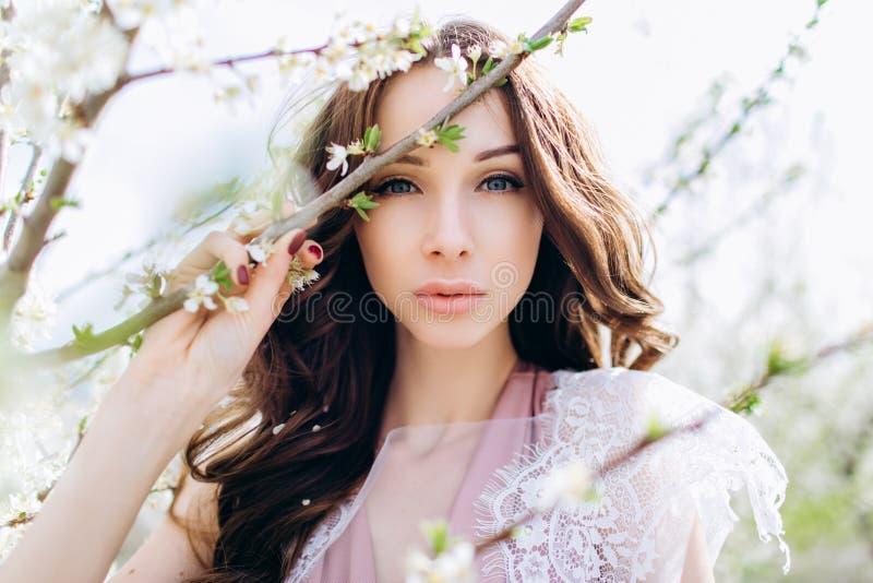 Moça em um jardim florescido branco dos pêssegos em um vestido e em uma composição brancos imagem de stock royalty free