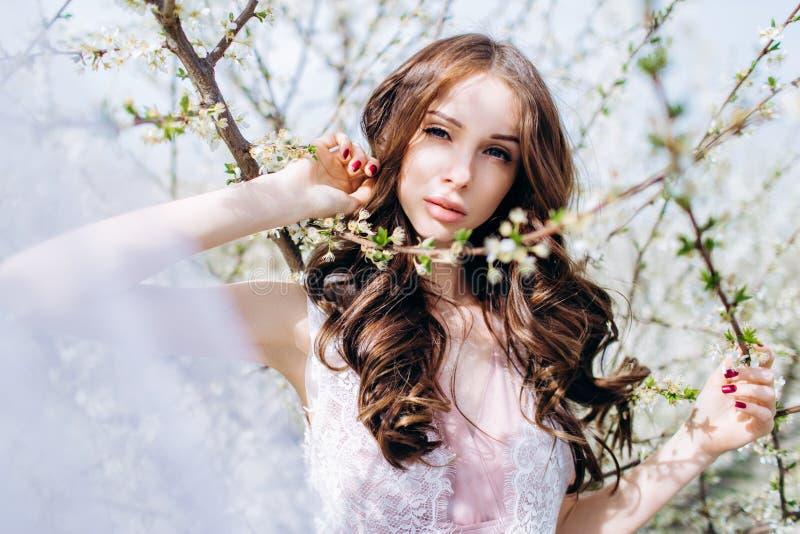 Moça em um jardim florescido branco dos pêssegos em um vestido e em uma composição brancos fotos de stock royalty free
