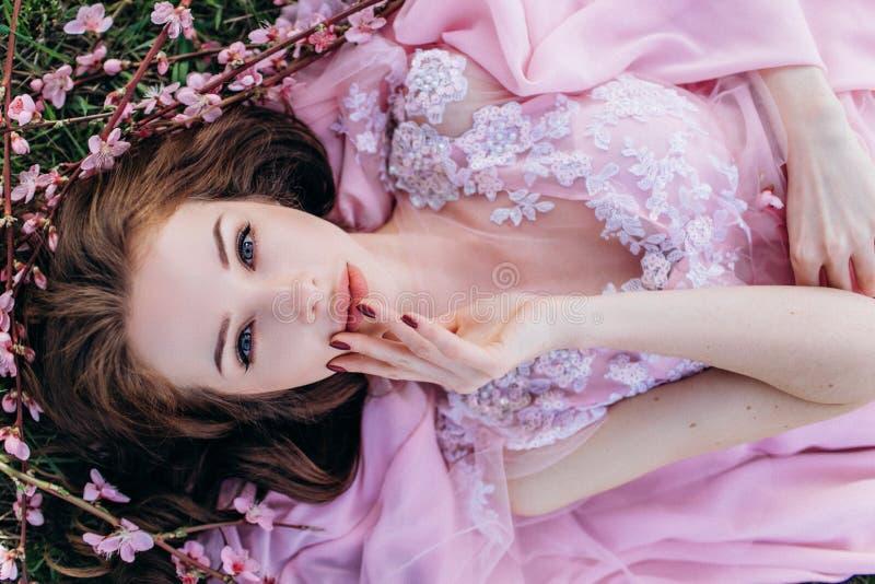 Moça em um jardim florescido cor-de-rosa dos pêssegos em um vestido e em uma composição cor-de-rosa fotografia de stock royalty free