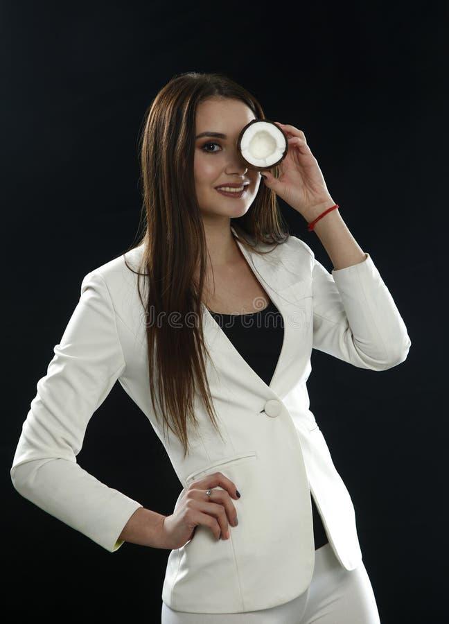 A moça em um revestimento branco guarda um coco perto de seu olho e sorri em um fundo preto imagem de stock royalty free