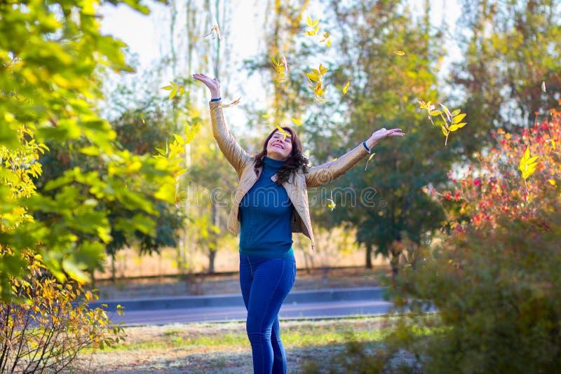 A moça em um revestimento do outono joga alegremente as folhas amarelas caídas-para baixo acima Caminhada no parque do outono imagem de stock royalty free