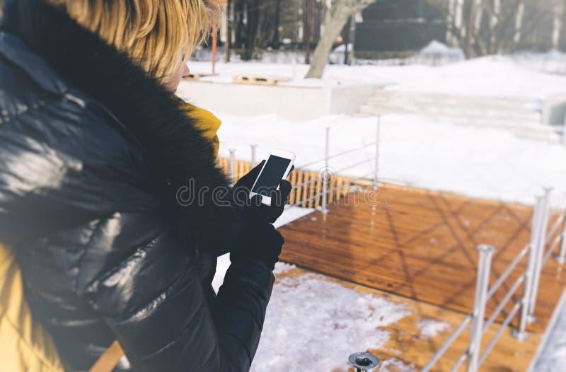Moça em um revestimento preto da pena e em uma trouxa amarela usando o smartphone com uma tela vazia limpa em um fundo do inverno foto de stock
