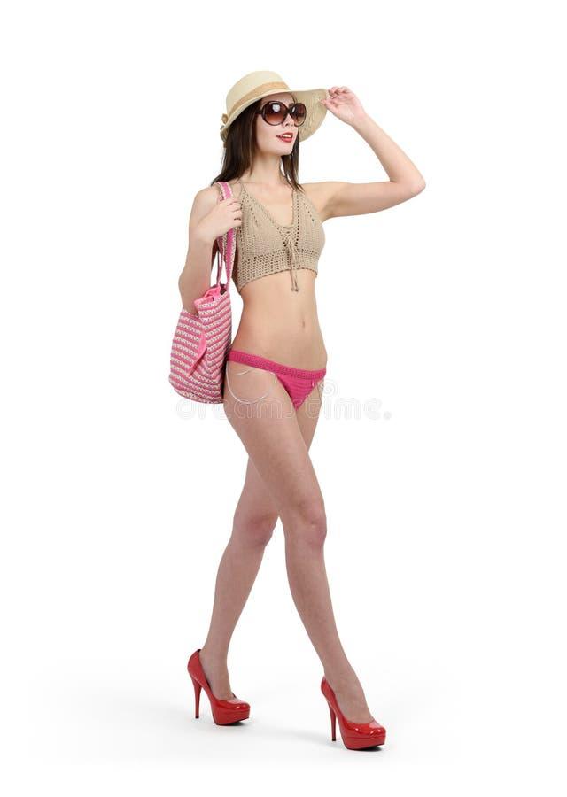 A moça em um roupa de banho, em óculos de sol e em um chapéu está andando em seus saltos No fundo branco foto de stock royalty free