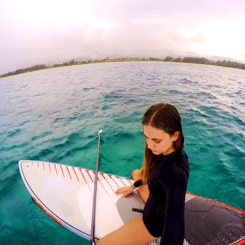Moça em um suporte acima da prancha em Havaí fotos de stock royalty free