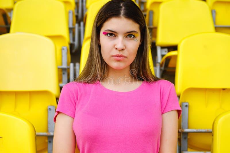 A moça em um t-shirt cor-de-rosa senta-se em uma tribuna vazia do estádio fotos de stock