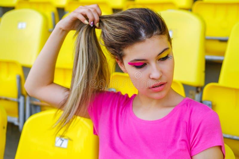 A moça em um t-shirt cor-de-rosa senta-se em uma tribuna vazia do estádio fotos de stock royalty free