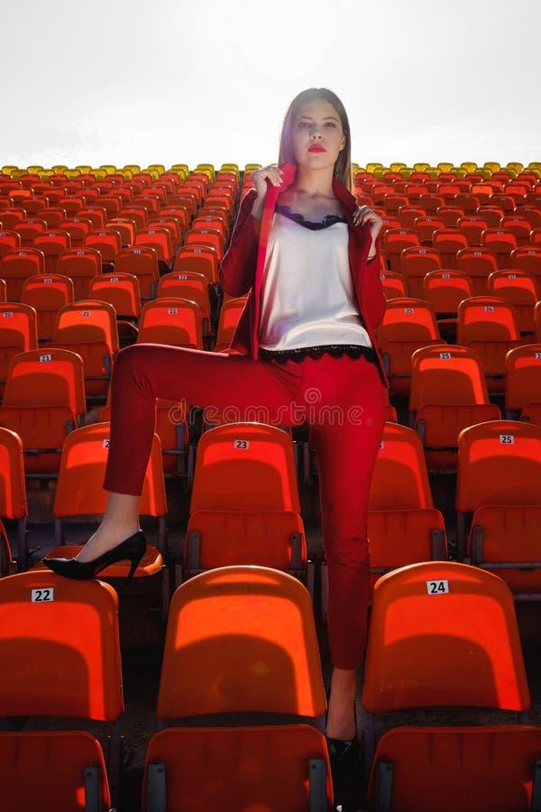 A moça em um terno vermelho está no pódio do estádio fotografia de stock