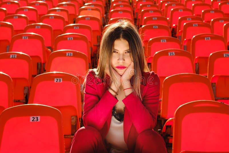 A moça em um terno vermelho senta-se no pódio do estádio imagem de stock royalty free