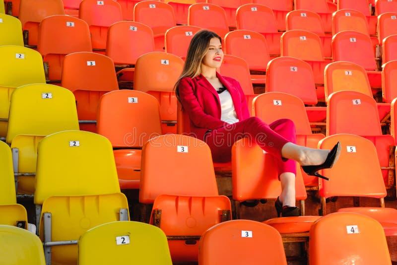 A moça em um terno vermelho sorri e senta-se em uma tribuna vazia do estádio foto de stock royalty free