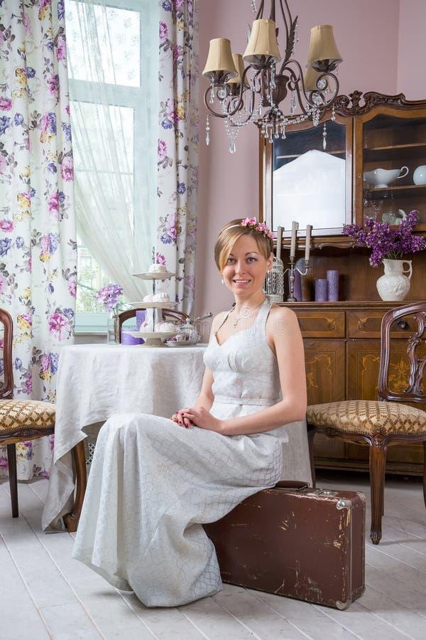A moça em um vestido de casamento retro do estilo está sentando-se em um suitca imagens de stock royalty free