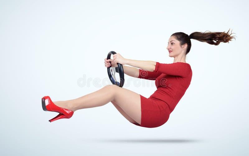 Moça em um vestido vermelho com um volante do carro imagens de stock
