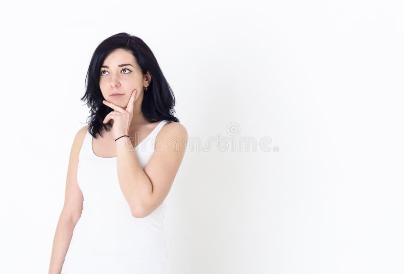 Moça em uma camisa branca que olha pensativamente acima com sua mão perto da cara fotografia de stock royalty free