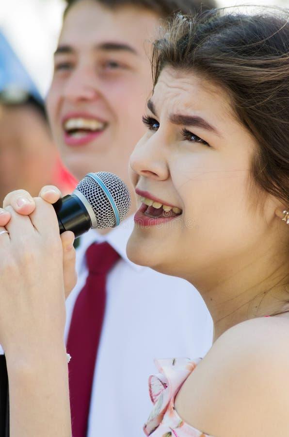 Moça em uma competição do karaoke em um parque da cidade Close-up imagens de stock